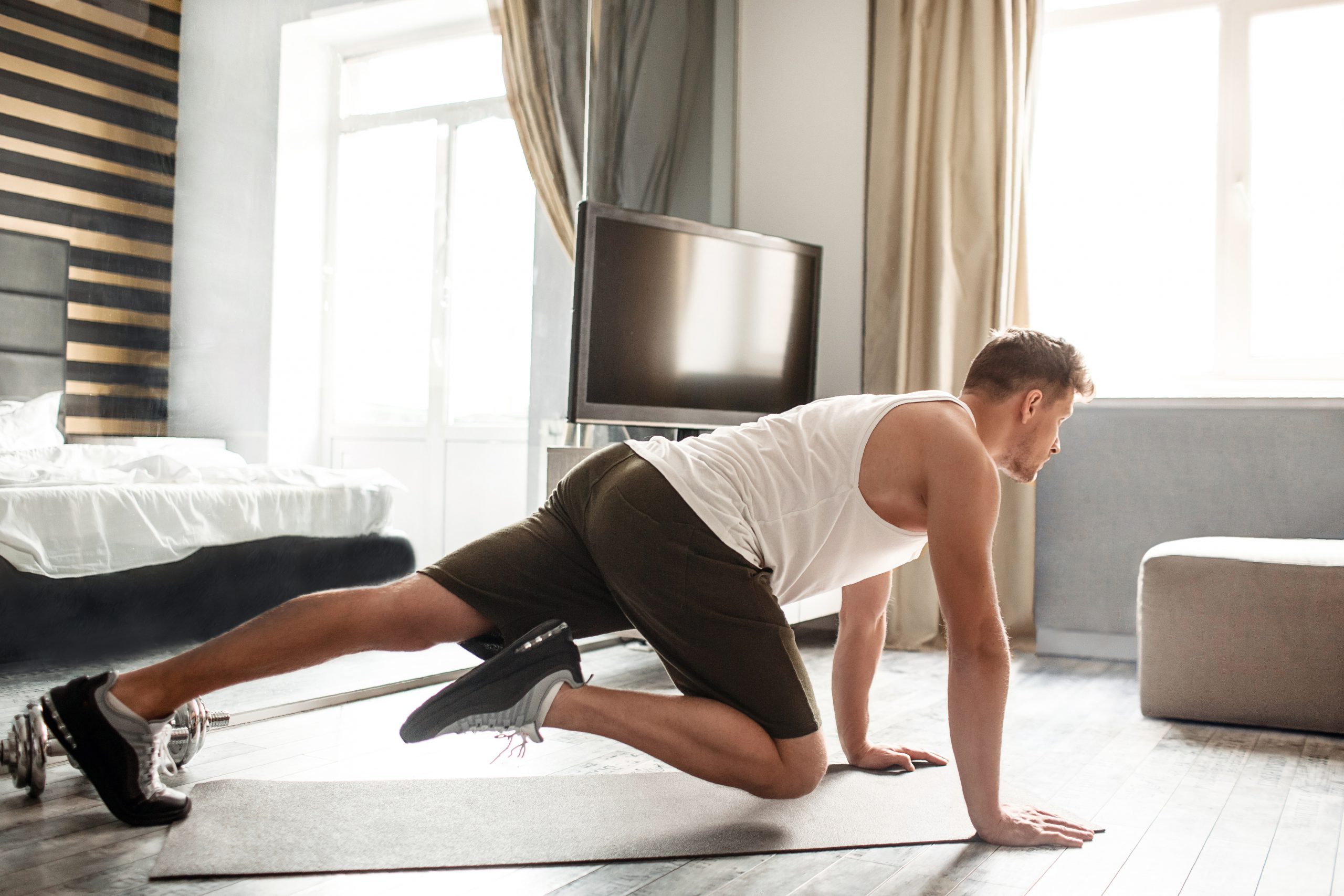 Young well-built man go in for sports in apartment. He stand on hands and move legs. Guy look straight forward. He exercise alone in room.