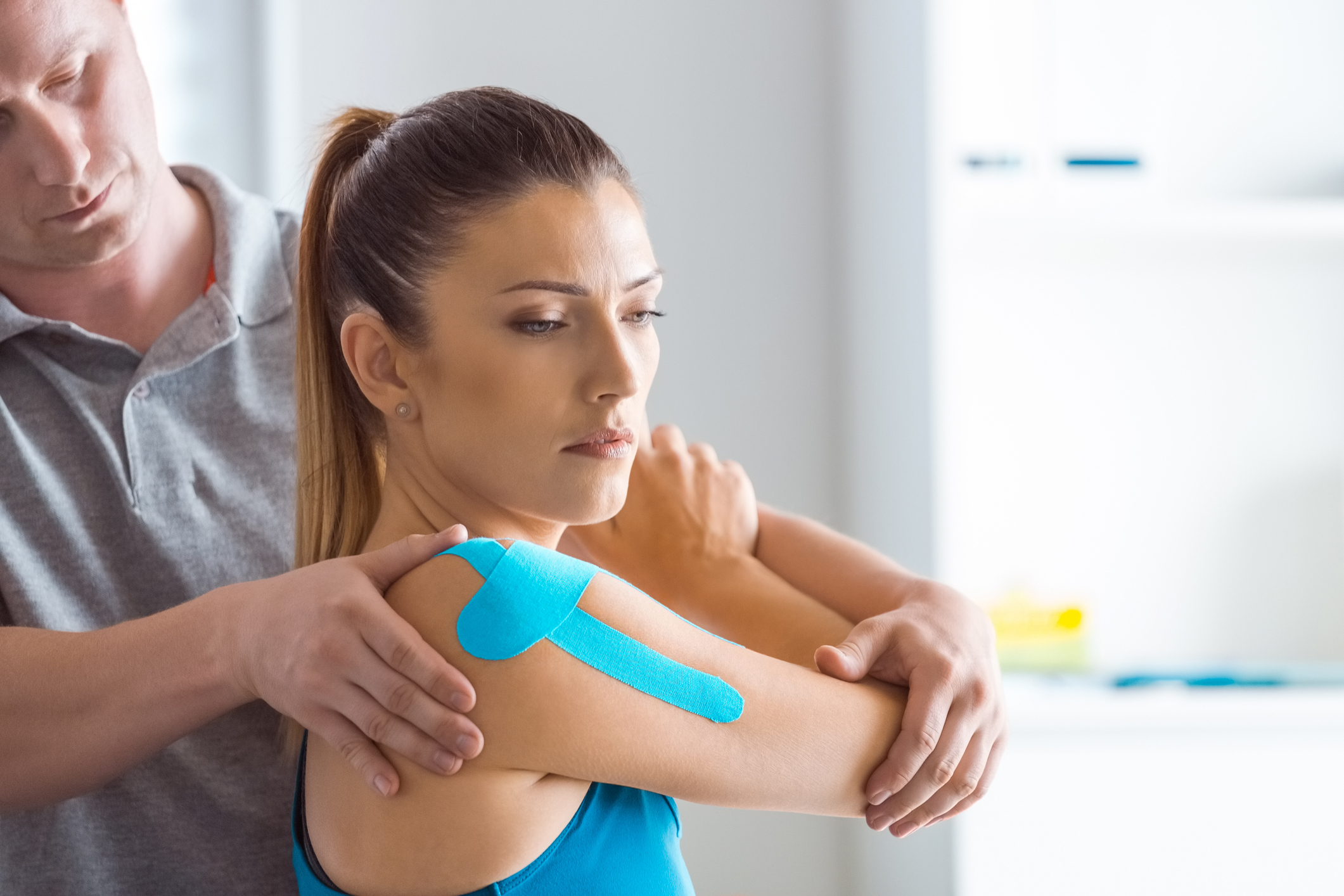 Physiotherapist massaging young woman