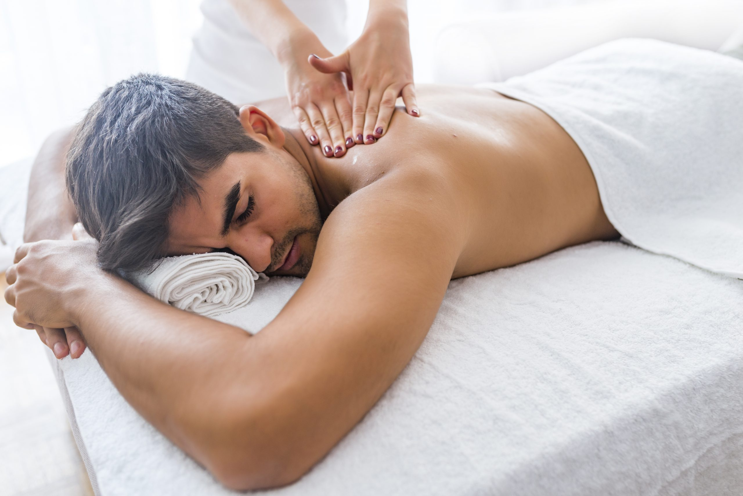 Young man is enjoying massage on spa treatment