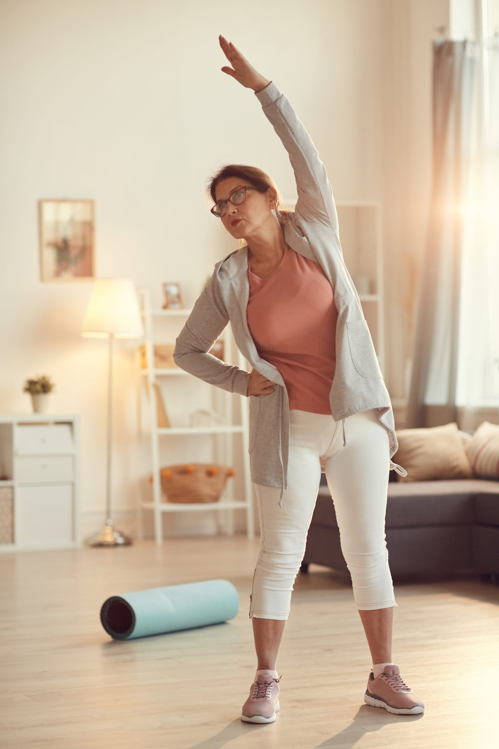 Serious purposeful senior woman in leggings standing in living room and doing side bend exercise alone