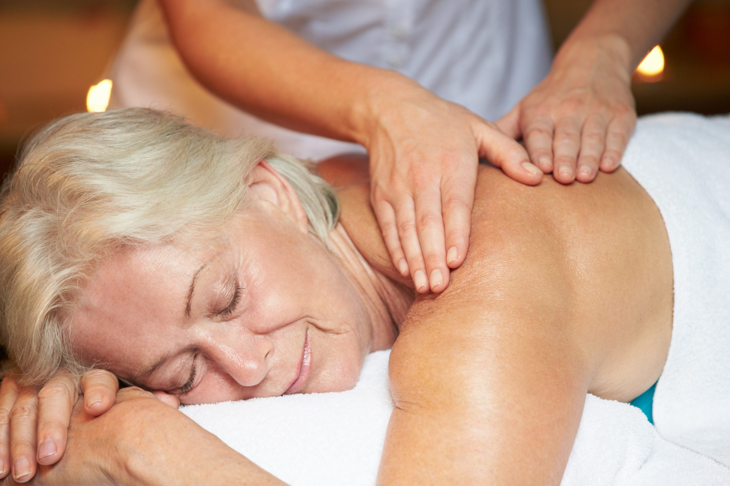 Smiling senior woman receiving a massage at the spa